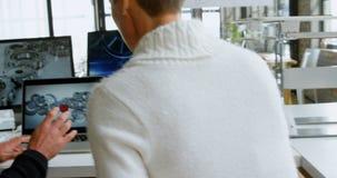 Σχεδιαστές αυτοκινήτων που συζητούν πέρα από το lap-top στο γραφείο 4k απόθεμα βίντεο