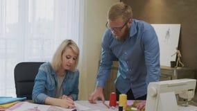 Σχεδιαστές μόδας που έχουν τη διασκέδαση εργαζόμενος σε ένα νέο φόρεμα απόθεμα βίντεο
