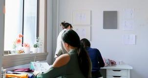 Σχεδιαστές μόδας που εργάζονται μαζί στο στούντιο σχεδίου 4k απόθεμα βίντεο