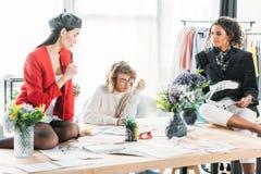 Σχεδιαστές μόδας που εργάζονται με τα σκίτσα Στοκ Φωτογραφίες