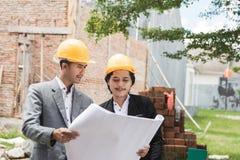 Σχεδιαστές που συζητούν το σχέδιο κατασκευής σπιτιών Στοκ Εικόνες
