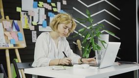 Σχεδιαστής γυναικών που εργάζεται σε ένα lap-top με μια ταμπλέτα γραφικής παράστασης φιλμ μικρού μήκους