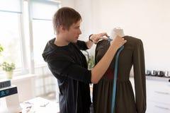 Σχεδιαστής μόδας με το ομοίωμα που κάνει το φόρεμα στο στούντιο Στοκ εικόνα με δικαίωμα ελεύθερης χρήσης