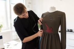 Σχεδιαστής μόδας με το ομοίωμα που κάνει το φόρεμα στο στούντιο Στοκ Φωτογραφίες
