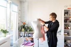 Σχεδιαστής μόδας με το ομοίωμα που κάνει το φόρεμα στο στούντιο Στοκ Εικόνες