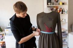 Σχεδιαστής μόδας με το ομοίωμα που κάνει το φόρεμα στο στούντιο Στοκ Φωτογραφία