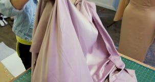 Σχεδιαστής μόδας που ελέγχει το ύφασμα στο στούντιο 4k μόδας απόθεμα βίντεο