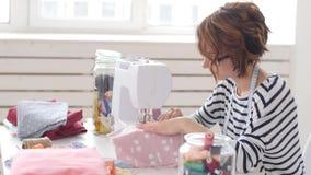 Έννοια μικρών επιχειρήσεων και χόμπι Σχεδιαστής μόδας που εργάζεται στα σχέδιά της στο φωτεινό στούντιο απόθεμα βίντεο