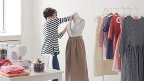 Έννοια μικρών επιχειρήσεων και χόμπι Σχεδιαστής μόδας που εργάζεται στα σχέδιά της στο φωτεινό στούντιο φιλμ μικρού μήκους