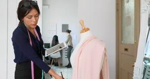 Σχεδιαστής μόδας που χρησιμοποιεί την ταμπλέτα εργαζόμενος σε ένα ύφασμα στις μοδίστρες πρότυπο 4k απόθεμα βίντεο