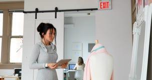 Σχεδιαστής μόδας χρησιμοποιώντας την ταμπλέτα και εξετάζοντας το ύφασμα στις μοδίστρες πρότυπο 4k απόθεμα βίντεο