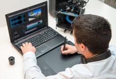 Σχεδιαστής νεαρών άνδρων που χρησιμοποιεί την ταμπλέτα γραφικής παράστασης για την τηλεοπτική έκδοση Στοκ εικόνες με δικαίωμα ελεύθερης χρήσης