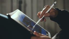 Σχεδιαστής που επισύρει την προσοχή και που ξελεπιάζει στην ταμπλέτα του που χρησιμοποιεί stylus απόθεμα βίντεο
