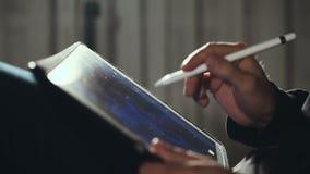 Σχεδιαστής που επισύρει την προσοχή και που ξελεπιάζει στην ταμπλέτα του που χρησιμοποιεί stylus φιλμ μικρού μήκους
