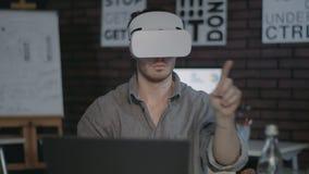 Σχεδιαστής που φορά vr τα προστατευτικά δίοπτρα Προγραμματιστής που χρησιμοποιεί vr τα γυαλιά στο σκοτεινό γραφείο φιλμ μικρού μήκους