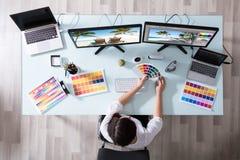 Σχεδιαστής που χρησιμοποιεί Swatch χρώματος εργαζόμενος στον πολλαπλάσιο υπολογιστή στοκ εικόνες