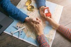 Σχετικά με τη στιγμή ο τύπος που προτείνει στον πίνακα με το χάρτη και το δαχτυλίδι στο κιβώτιο Το ταξίδι το νέο ζεύγος στοκ εικόνες