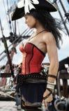 Σχεδιάγραμμα ενός προκλητικού θηλυκού καπετάνιου πειρατών που στέκεται στο κατάστρωμα του πλοίου της Πιστόλι και ξίφος υπό εξέτασ διανυσματική απεικόνιση