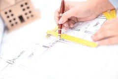 Σχεδιάγραμμα του κτιρίου γραφείων πέρα από το θολωμένο ενήλικο αρσενικό μηχανικό που εξετάζει τα έγγραφα Στοκ Φωτογραφία