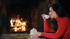 Σχεδιάγραμμα του brunette στο κόκκινο πουλόβερ, τσάι κατανάλωσης εσωτερικό φιλμ μικρού μήκους