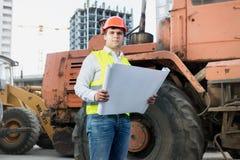 Σχεδιαγράμματα ανάγνωσης αρχιτεκτόνων δίπλα στον εκσακαφέα στο εργοτάξιο Στοκ Εικόνες