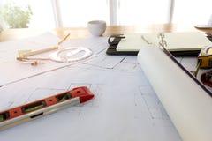 Σχεδιαγράμματα, Hardhat, γυαλιά, αυτοκόλλητες ετικέττες, επίπεδο κατασκευής, μάνδρα στο γραφείο αρχιτεκτονικής Στοκ Φωτογραφία