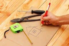 Σχεδιασμός ενός σχεδίου οικοδόμησης με το κόκκινο μολύβι Στοκ εικόνα με δικαίωμα ελεύθερης χρήσης
