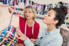 Σχεδιαστής που εργάζεται dressmaking στο στούντιο με το cowoker Στοκ Φωτογραφία