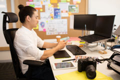 Σχεδιαστής που χρησιμοποιεί το τηλέφωνο στο δημιουργικό γραφείο γραφείων Στοκ Εικόνα