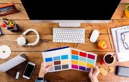 Σχεδιαστής στο γραφείο γραφείων που λειτουργεί με swatches χρώματος Στοκ Εικόνες