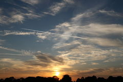Σχεδόν θέστε τον ήλιο στους νεφελώδεις ουρανούς με τα ίχνη αεροπλάνων Στοκ Φωτογραφία