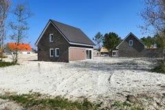 Σχεδόν τελειωμένα νέα σπίτια που στηρίζονται σε ένα εργοτάξιο οικοδομής Στοκ Εικόνα