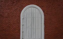 Σχηματισμένη αψίδα άσπρη πόρτα στον τούβλινο τοίχο Στοκ εικόνες με δικαίωμα ελεύθερης χρήσης
