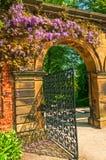 Σχηματισμένη αψίδα ο Stone πύλη κήπων που περιβάλλεται από τα λουλούδια Στοκ Φωτογραφία