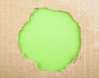 Σχισμένη τρύπα στο χαρτόνι στο ροζ Στοκ Φωτογραφίες