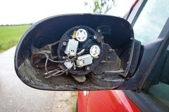 Σχισμένος από το σπασμένο δευτερεύοντα καθρέφτη με να λείψει γυαλιού και τα καλώδια που κολλούν έξω στο κόκκινο αυτοκίνητο στοκ φωτογραφίες