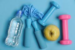 Σχοινί άλματος, μήλο και barbells δίπλα στο μπουκάλι νερό στοκ εικόνα με δικαίωμα ελεύθερης χρήσης