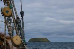 Σχοινιά ενός αρχαίου whaler στο πρώτο πλάνο και στο υπόβαθρο το νησί όπου τα puffins ζουν στοκ εικόνα