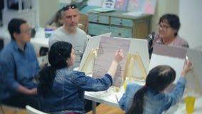 Σχολείο τέχνης, δημιουργικότητα και έννοια ανθρώπων - ομάδα σπουδαστών με easels, τα πινέλα και τις παλέτες που χρωματίζουν ακόμα απόθεμα βίντεο