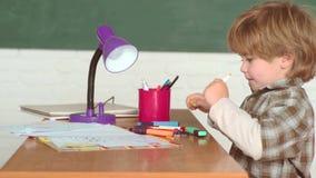Σχολικά παιδιά ενάντια στον πράσινο πίνακα κιμωλίας Σχολείο και παιδιά βιβλίων preschooler o Ευτυχής διάθεση που χαμογελά ευρέως  απόθεμα βίντεο