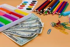Σχολικά προμήθειες και δολάρια Στοκ Εικόνες
