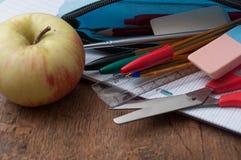 σχολικά προμήθειες και μήλο στο ξύλινο υπόβαθρο γραφείων Στοκ φωτογραφία με δικαίωμα ελεύθερης χρήσης