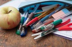 σχολικά προμήθειες και μήλο στο ξύλινο υπόβαθρο γραφείων Στοκ Φωτογραφίες
