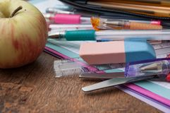 σχολικά προμήθειες και μήλο στο ξύλινο υπόβαθρο γραφείων Στοκ εικόνες με δικαίωμα ελεύθερης χρήσης