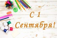 Σχολικές προμήθειες σε ένα άσπρο ξύλινο υπόβαθρο με την επιγραφή στα ρωσικά την 1η Σεπτεμβρίου Στοκ Εικόνες