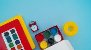 Σχολικές προμήθειες στο μπλε υπόβαθρο πίσω σχολείο kindergarten στοκ εικόνα