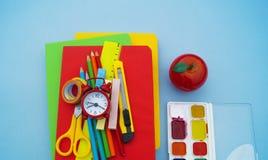 Σχολικές προμήθειες στο μπλε υπόβαθρο πίσω σχολείο kindergarten στοκ εικόνες
