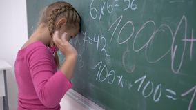 Σχολική εκπαίδευση, θηλυκός μαθητής που στέκεται κοντά στον πίνακα με τα παραδείγματα μαθηματικών απόθεμα βίντεο