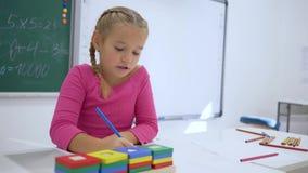 Σχολική ημέρα, ο θηλυκός μαθητής γράφει έναν στόχο στο copybook στο γραφείο σε μια τάξη στο υπόβαθρο του πίνακα απόθεμα βίντεο