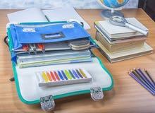 Σχολική τσάντα με τα βιβλία, τα σημειωματάρια, το στυλό και τα μολύβια Στοκ Φωτογραφία